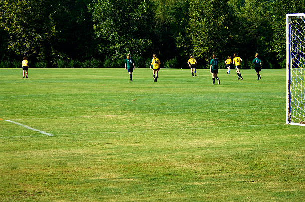 two soccer teams playing a game on a bright green field  - soccer competition stock photos and pictures