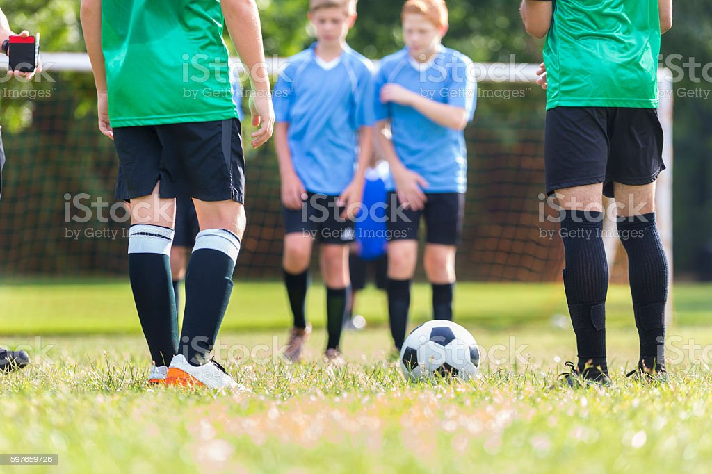 Diverse teenage boys\' soccer teams prepare to start the game. Boys in...