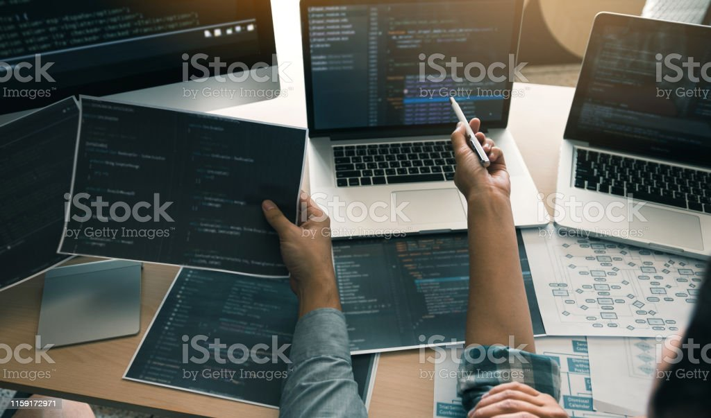 Two software developers are using computers to work together with...