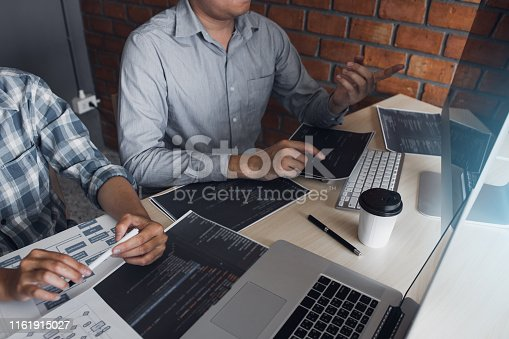 istock Two software developers are using computers to work together with their partner at the office desk. 1161915027