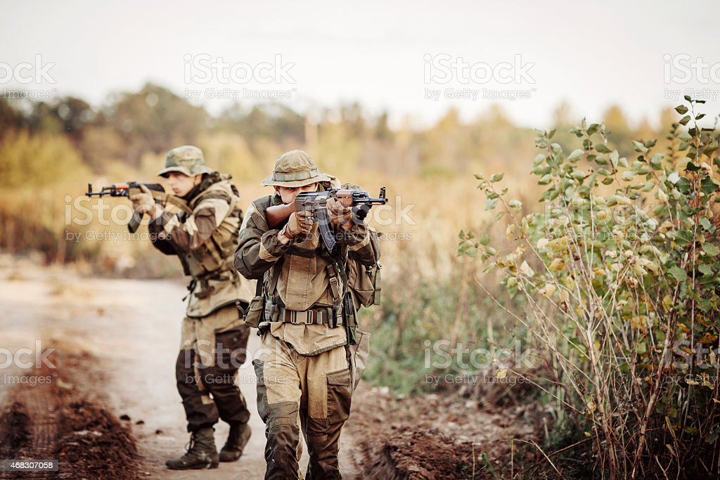 Two soldiers are exploring an unfamiliar area stock photo