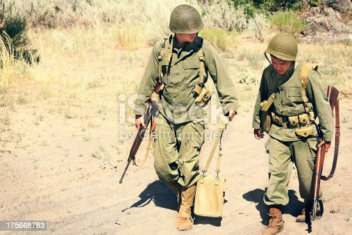 Two soldiers walking along a dusty road. Vintage, authentic army uniforms and weapons.