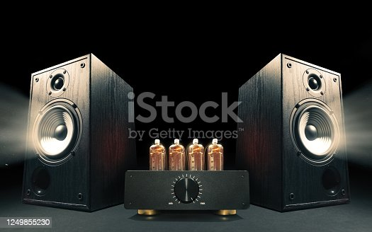 Two sound speakers with vacuum tube amplifier between them on black background.