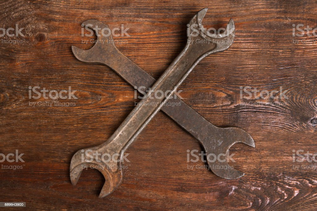 two spanners wooden background service maintenance stock photo