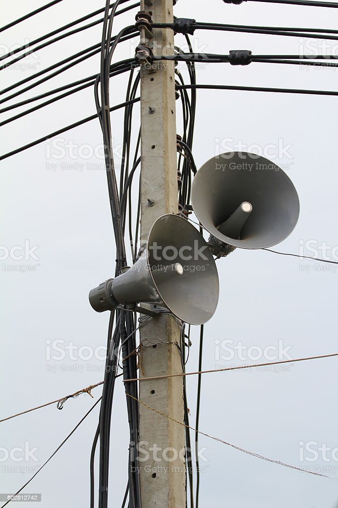Two speakers are installed on a concreat pole wires against. stock photo