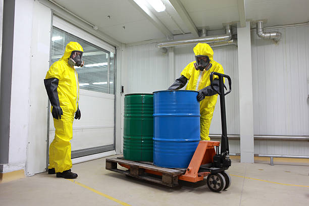 Two specialists dealing with barrels of chemicals Two specialists in protective uniforms,masks,gloves and boots  dealing with barrels of chemicals on forklift in factory hazardous chemicals stock pictures, royalty-free photos & images