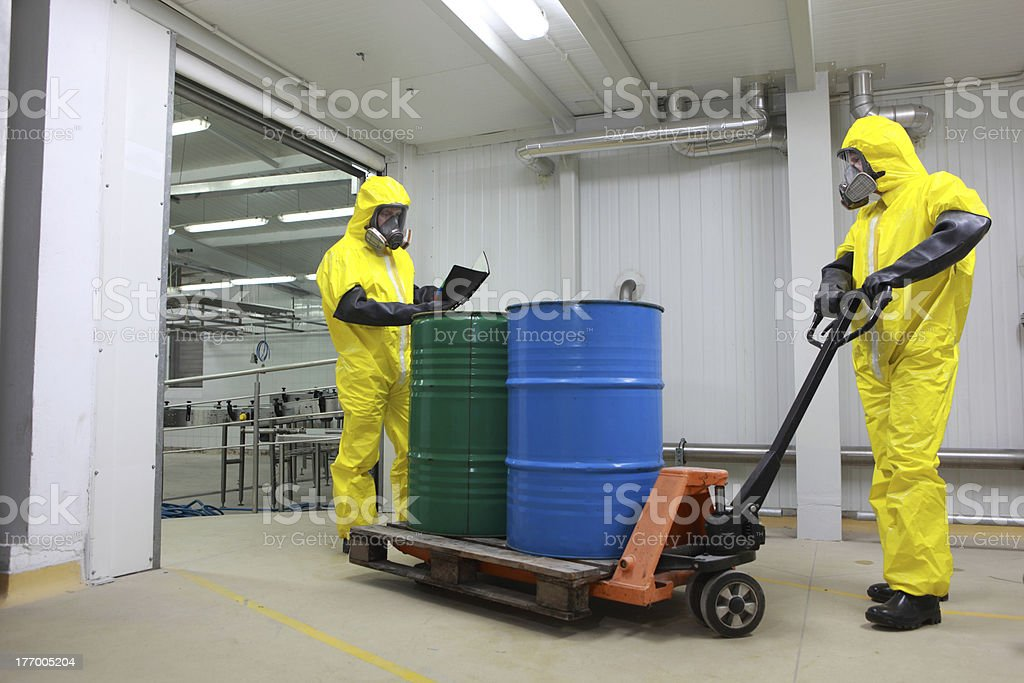 Two specialists dealing with barrels of toxic waste  in factory royalty-free stock photo