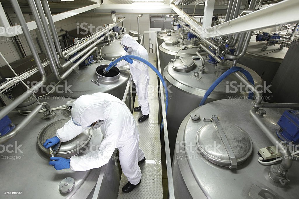Two specialists in  overalls working with industrial process tanks stock photo