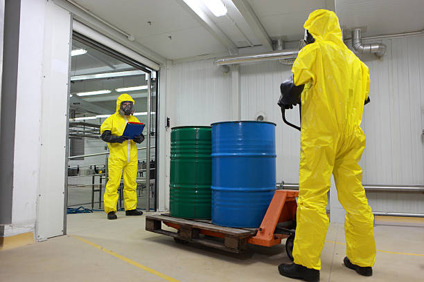 Two specialists in protective uniforms dealing with toxic substance stock photo