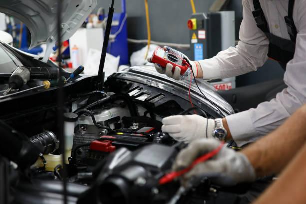 zwei spezialisten für den service für die reparatur von verdrahtung - autowerkstatt stock-fotos und bilder