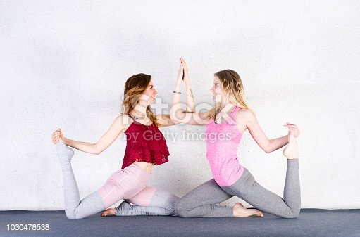 916126642istockphoto Two sports girls train yoga in a fitness class. Group of young women stretching in gym 1030478538
