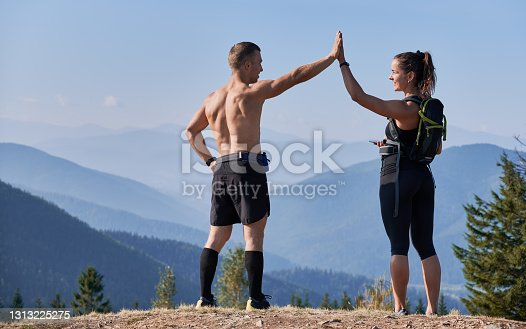 istock Two sports people admiring mountain landscape from top of one hill. 1313225275