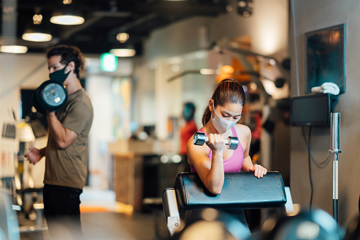 Two sports persons are wearing protective face masks and training in a gym while keeping social distancing.