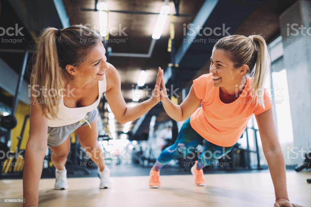 Two sporty girls doing push ups in gym stock photo