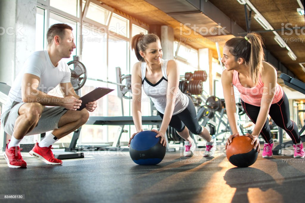Two sporty girls exercising with fitness balls while their fitness instructor tracking the progress on clipboard. - foto stock
