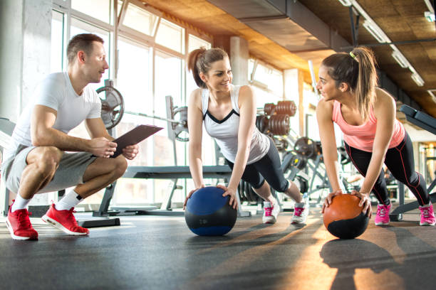 two sporty girls exercising with fitness balls while their fitness instructor tracking the progress on clipboard. - health club stock photos and pictures