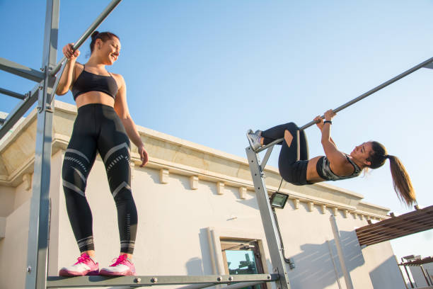 two sporty girls having fun during calisthenics training outdoors. - horizontal bar stock photos and pictures