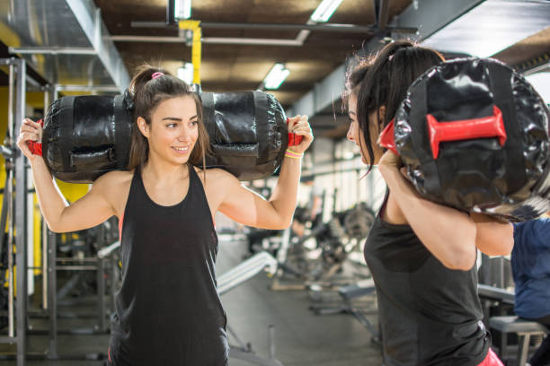 Two sporty women working out together with strength bags in the gym. stock photo