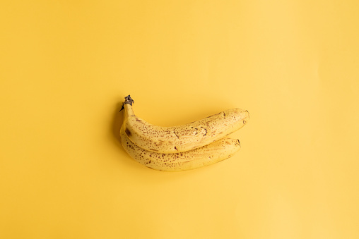 istock Two spotty bananas on yellow background from above 1060636704