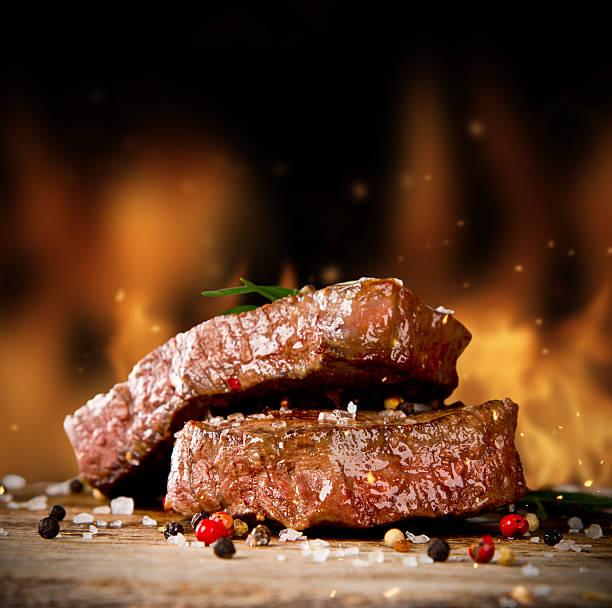 two stacked beef steaks with flames in background  - vleesdelen stockfoto's en -beelden