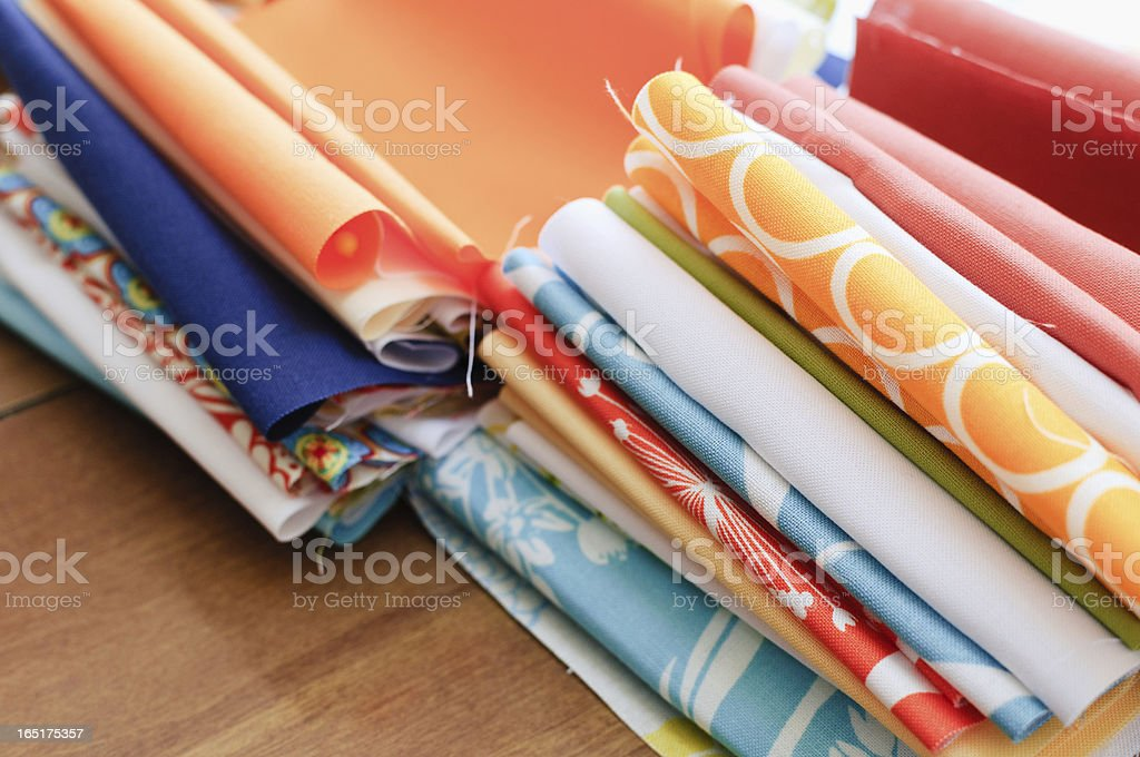 Two stacks of colorful quilting fabrics on the floor stock photo