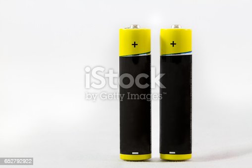 istock Two standing yellow-black AAA alkaline batteries isolated on white 652792922