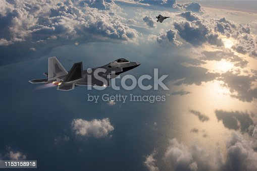 istock Two Stealth Jet Fighters in Flight at sunset 1153158918