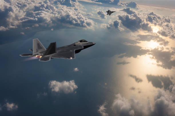 Two Stealth Jet Fighters in Flight at sunset stock photo