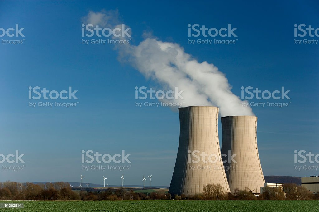 Two Steaming cooling towers and wind turbine farm royalty-free stock photo