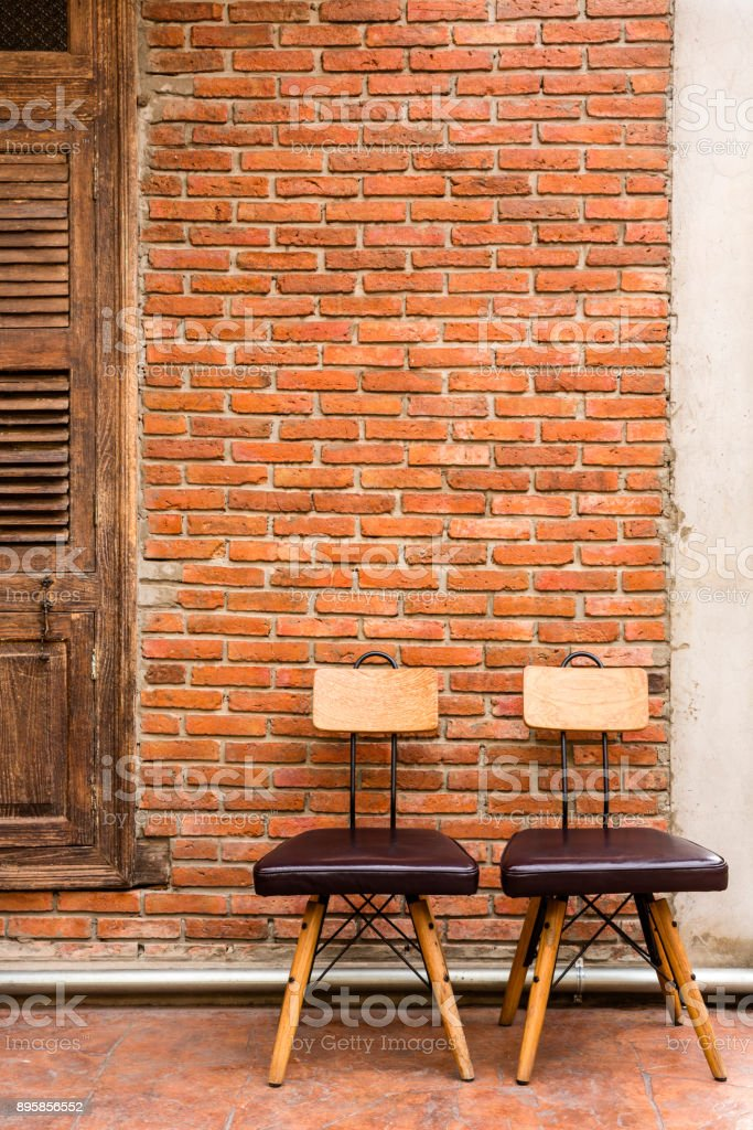 Two steel frame chairs are padded with brown cushions and a wooden backrest stock photo
