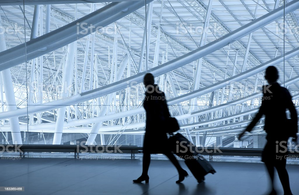 Two Stewardesses Walking at Airport, Pulling Luggage royalty-free stock photo