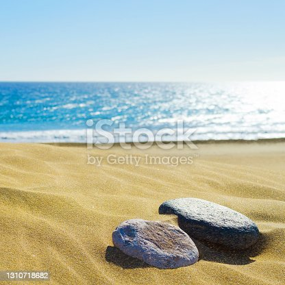 Two stones on the sandy shore of the ocean. Square orientation. Natural background.