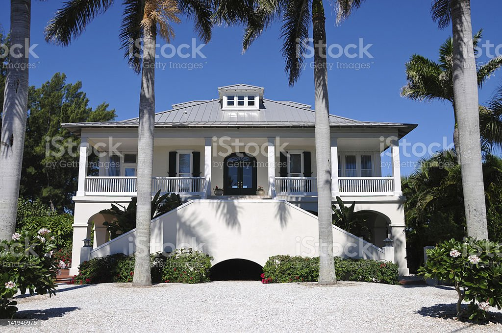 Two story beach house with large front porch and palm trees stock photo