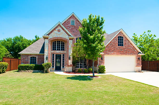 Two story brick residential home Two story brick residential home with the garage in the front. stone house stock pictures, royalty-free photos & images