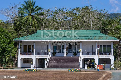 Puerto Princesa, Palawan, Philippines - March 3, 2019: Iwahig Penal Colony. Two story white office buildig with green corrugated roof, backed by green foliage under blue sky.