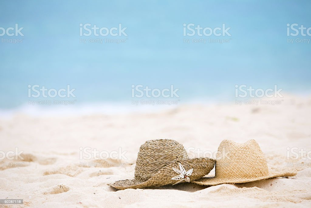 Two straw hats sit on a white sand beach next to the ocean stock photo