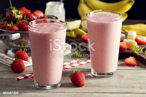 istock Two Strawberry Banana Yogurt Smoothies in Glasses with Ingredients 483467404