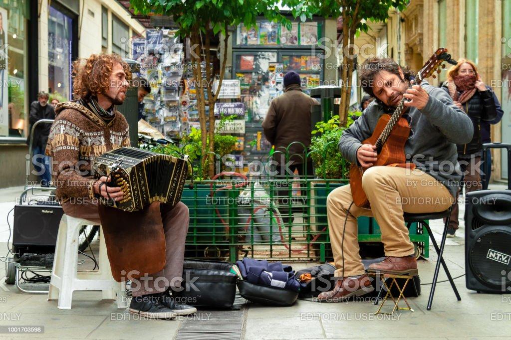 Dos músicos callejeros tocan tango con bandoneón y guitarra en la calle Florida en Buenos Aires - foto de stock