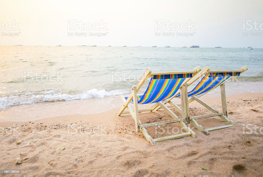 Two striped beach chairs on the sand by the water royalty-free stock photo