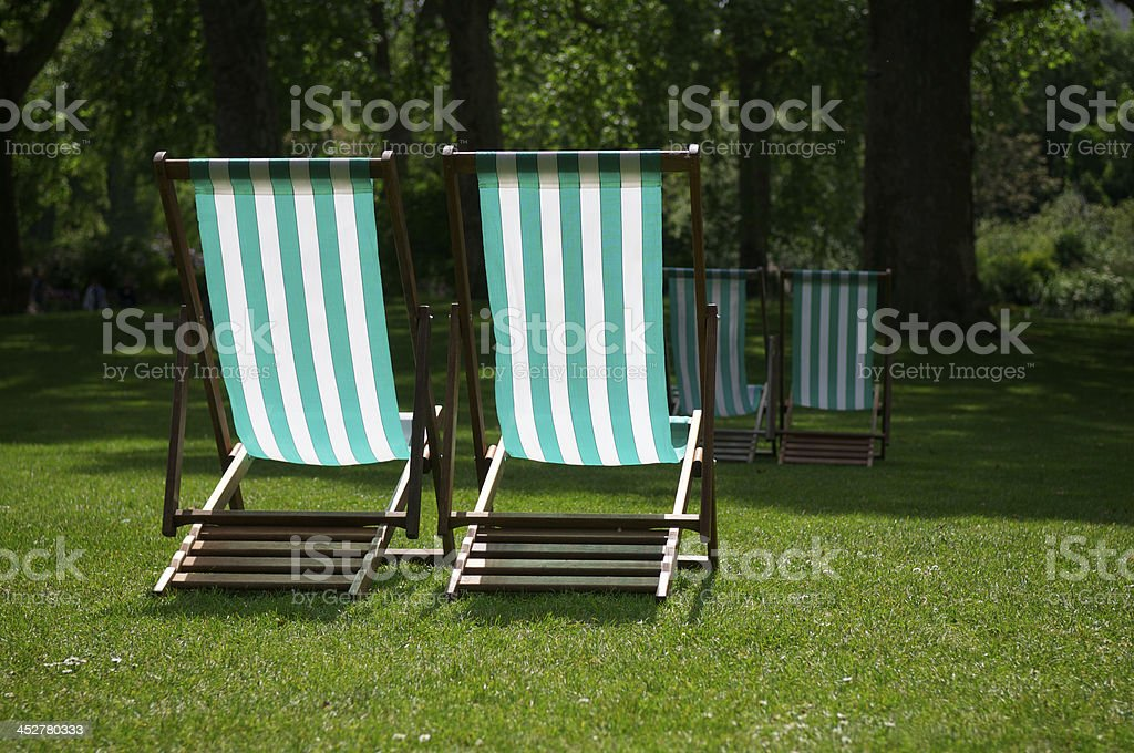Two Striped Deck Chairs on Grass of Sunny Park royalty-free stock photo