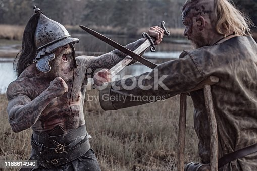 Two strong viking men fighting in hand to hand combat on a battlefield