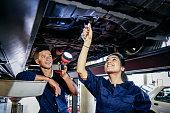 istock Two student mechanics repairing car, woman using spanner 827810800