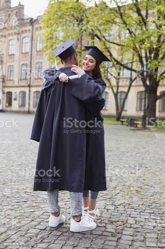 Two students in mortarboards hugging royalty-free stock photo