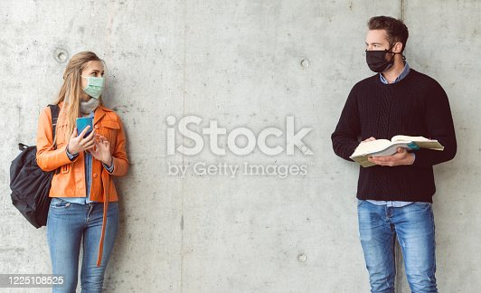 Two students standing in social distance wearing face mask looking at each other