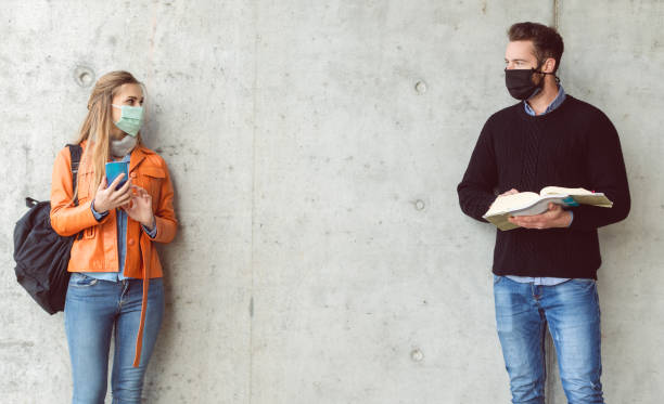 Two students standing in social distance wearing face mask stock photo