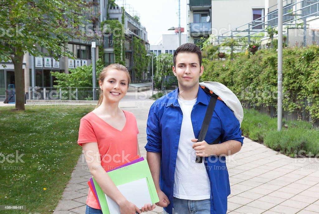 Dos estudiantes en el campus de pie - foto de stock