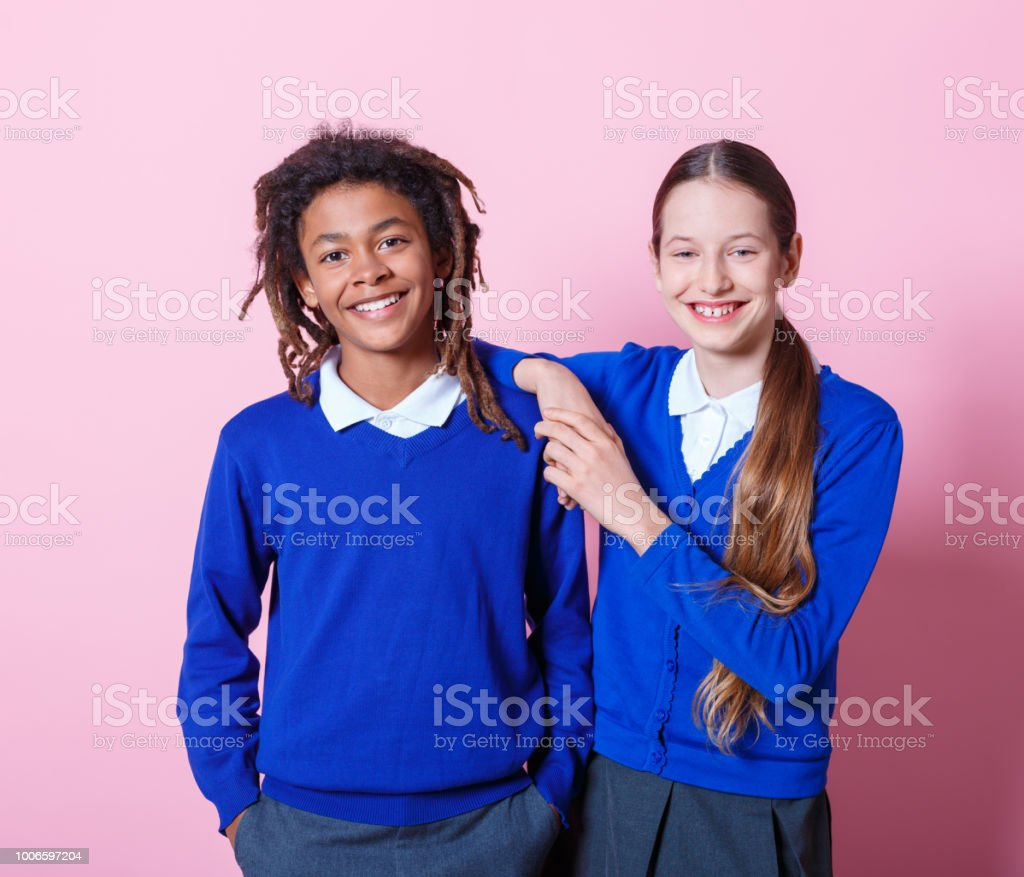 Two students standing togehter Two students standing together on pink background. Teenage boy and girl in school uniform looking at camera and smiling. 12-13 Years Stock Photo