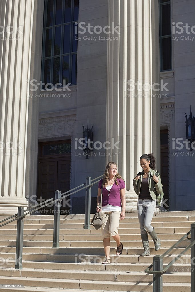 Two Students Walking Outside Academic Hall in University Campus royalty-free stock photo