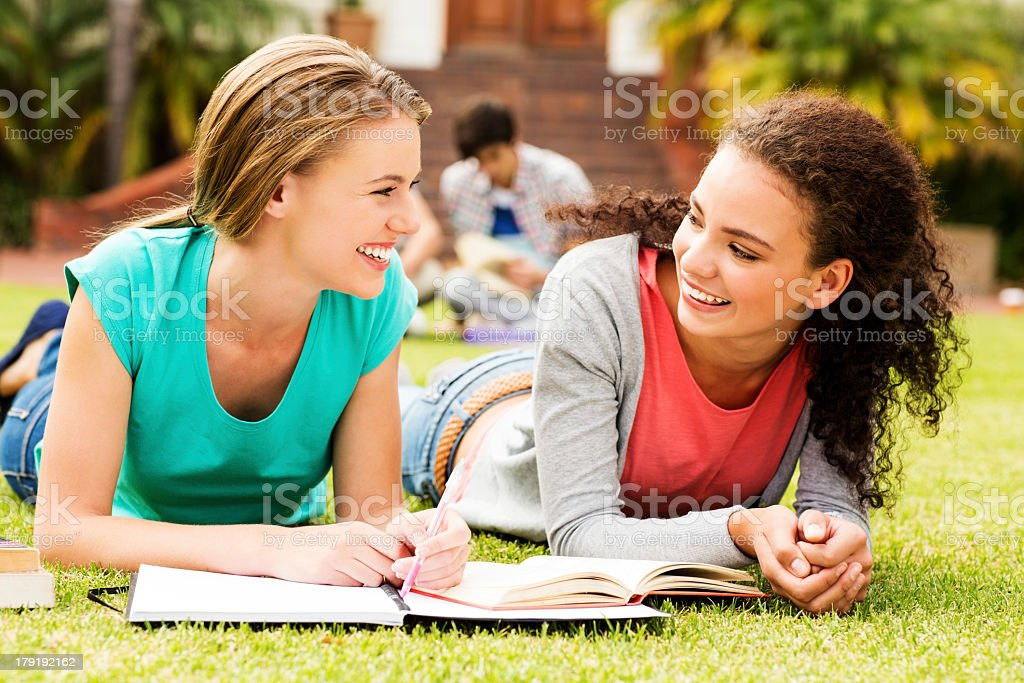 Two Students With Books Lying On University Campus royalty-free stock photo