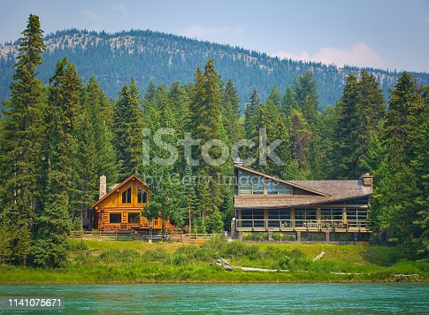 Two styles of wooden house commonly found near lakes and rivers. Rocky mountain ( Canadian Rockies ). Portrait, fine art. Near Calgary. Jasper and Banff National Park, Alberta, Canada: August 2, 2018